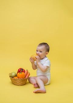 Un ragazzino con un cesto di frutta e verdura su uno spazio giallo. il bambino guarda e mangia un limone. orientamento verticale. copia spazio