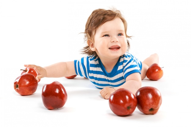 Un ragazzino con un mucchio di mele