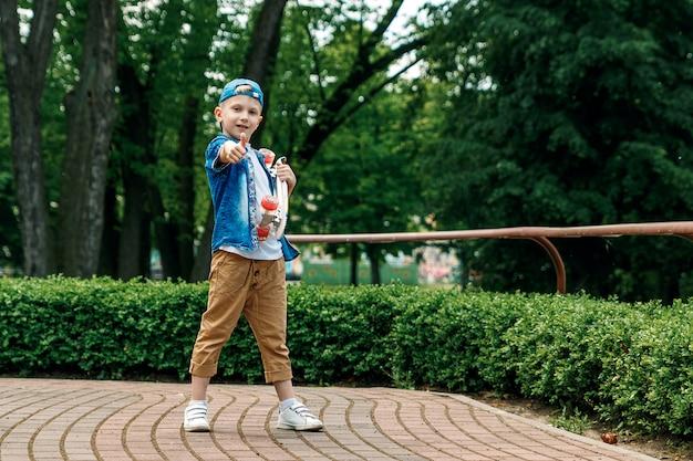 Un ragazzino di città e uno skateboard. un giovane ragazzo è in piedi nel parco e in possesso di uno skateboar