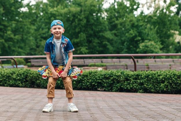 Un ragazzino di città e uno skateboard. un giovane ragazzo è in piedi nel parco e in possesso di uno skateboard