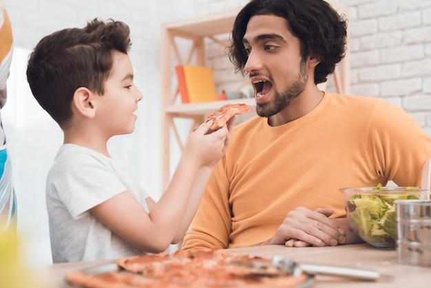 Un ragazzino e suo padre arabo mangiano insieme la pizza.