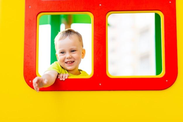 Un ragazzino gioca nel parco giochi nel cortile di casa d'estate, guardando fuori dalla finestra