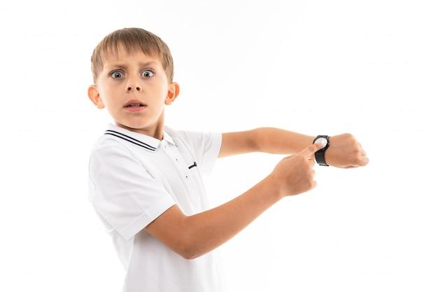 Un ragazzino in camicia bianca, pantaloncini blu con capelli biondi, si mette in mostra sul suo orologio da polso ed è spaventato