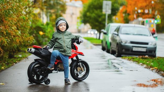 Un ragazzino in posa alla moto rossa dei suoi figli.