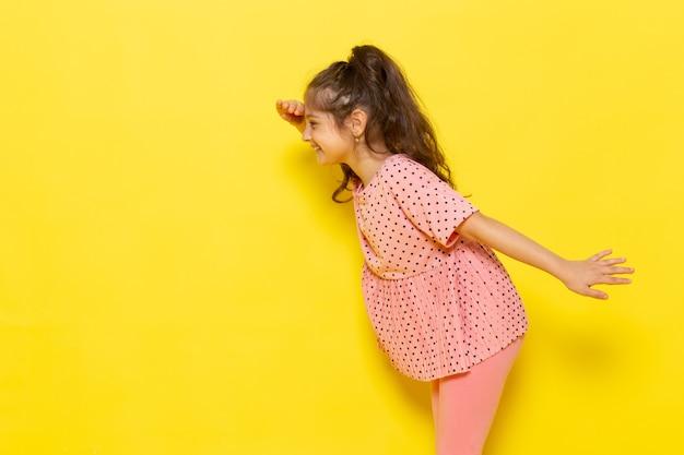 Un ragazzino sveglio di vista frontale in vestito rosa che esamina la distanza