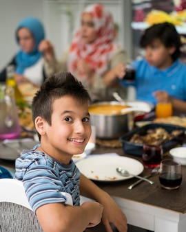 Un ragazzo a casa a pranzo con la sua famiglia e gli amici