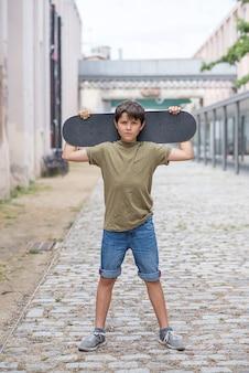 Un ragazzo adolescente che trasportano skateboard e sorridente