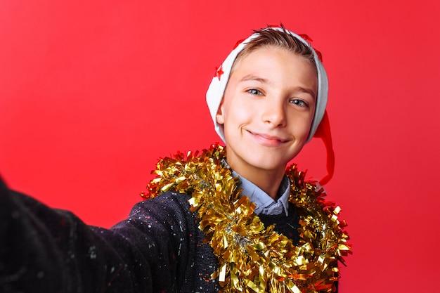 Un ragazzo adolescente fa un selfie con un cappello da babbo natale e orpelli sul collo