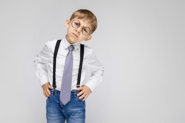 Un ragazzo affascinante con camicia bianca, bretelle, cravatta e jeans chiari si trova su uno sfondo grigio. il ragazzo con gli occhiali inclinò la testa di lato