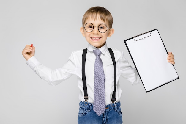 Un ragazzo affascinante con camicia bianca, bretelle, cravatta e jeans chiari si trova su uno sfondo grigio. il ragazzo tiene una penna e fogli per appunti