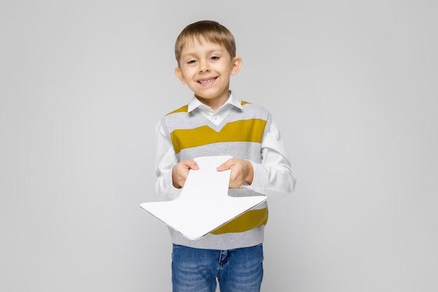 Un ragazzo affascinante con camicia bianca, canotta a righe e jeans chiari è in piedi su un grigio. il ragazzo tiene in mano una freccia bianca