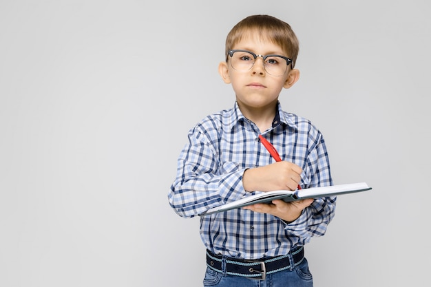 Un ragazzo affascinante con una camicia vkletchatoy e jeans chiari è in piedi su un grigio. il ragazzo tiene in mano un quaderno e una penna.