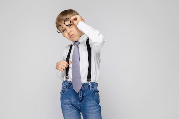 Un ragazzo affascinante in camicia bianca, bretelle, cravatta e jeans leggeri si leva in piedi sul grigio