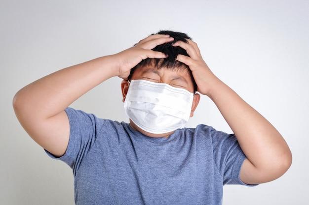 Un ragazzo asiatico indossa una maschera, coprendosi bocca e naso, prevenendo il coronavirus o covid-19. concetto di salute dei bambini