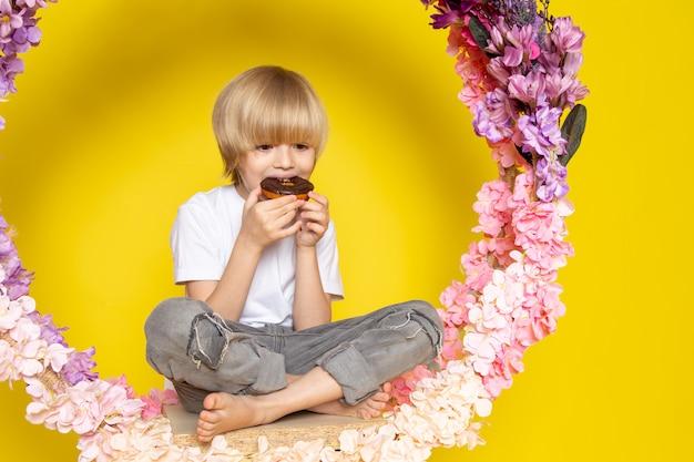 Un ragazzo biondo di vista frontale che mangia le ciambelle in maglietta bianca sullo scrittorio giallo