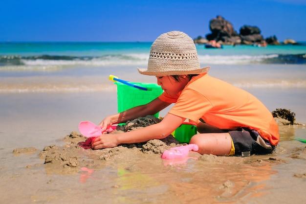 Un ragazzo carino asiatico che gioca la sabbia da solo sulla spiaggia.