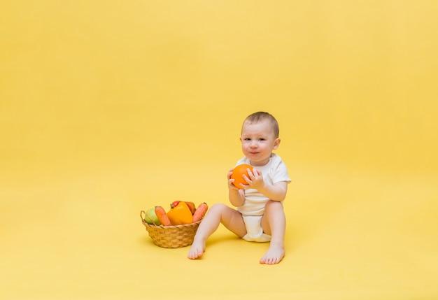 Un ragazzo carino è seduto in una tuta bianca e tiene in mano un'arancia. un bambino è seduto con un cesto di frutta e verdura su uno spazio giallo. il bambino sembra.