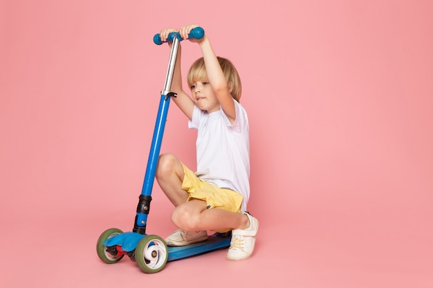 Un ragazzo carino vista frontale in maglietta bianca e jeans gialli in sella a scooter sullo spazio rosa
