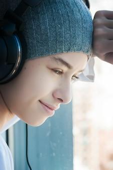 Un ragazzo che ascolta la musica mentre guarda fuori dalla finestra