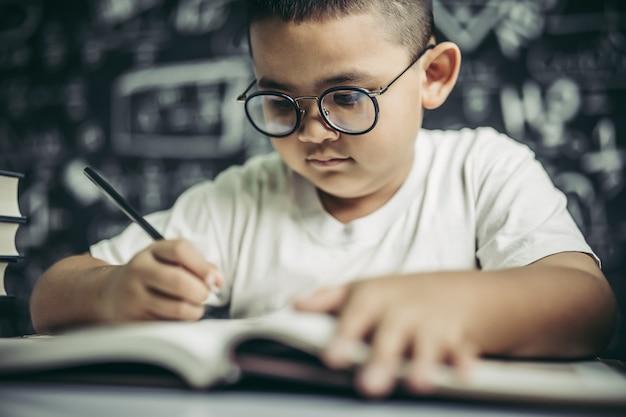 Un ragazzo con gli occhiali uomo che scrive in classe