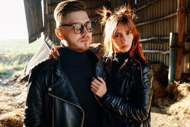 Un ragazzo con la barba sta con la sua ragazza in giacche di pelle nera in un granaio