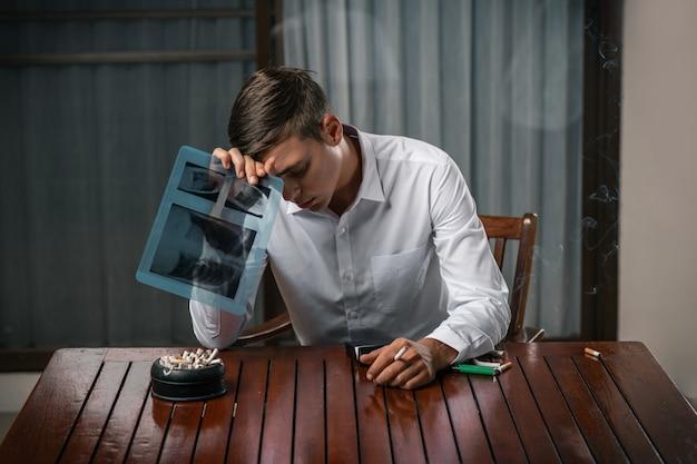 Un ragazzo con la testa si inchinò con una radiografia dei suoi polmoni, seduto a un tavolo con sopra un posacenere