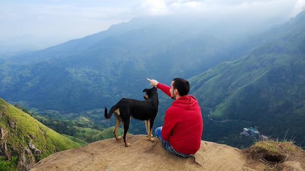 Un ragazzo con un cane che gode del paesaggio montano sul bordo di una scogliera
