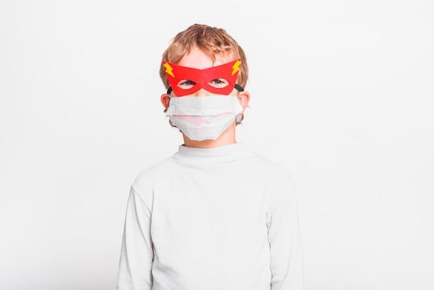 Un ragazzo con una divertente maschera da supereroe per proteggersi dalle infezioni virali della malattia.