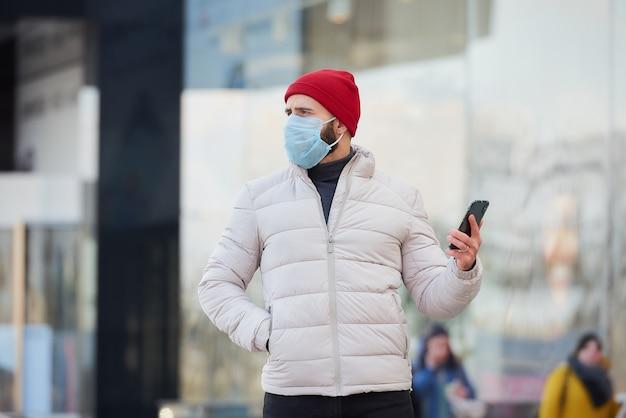 Un ragazzo con una maschera sul viso usando uno smartphone nel centro della città.