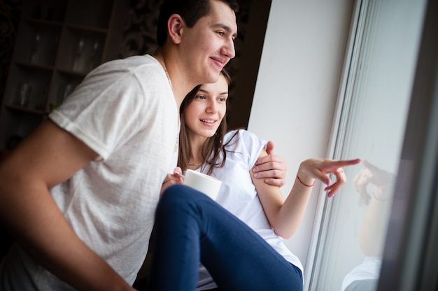 Un ragazzo con una ragazza che beve caffè vicino alla finestra