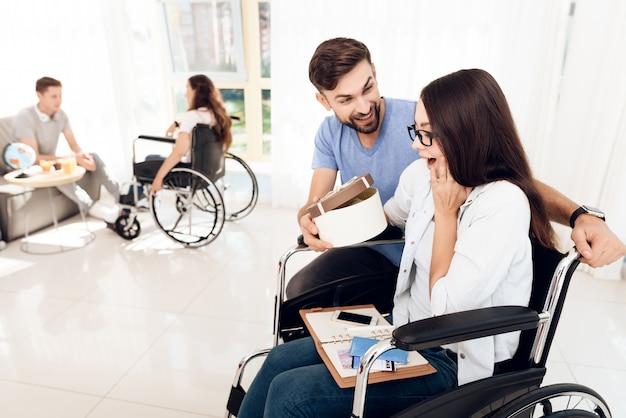 Un ragazzo con una ragazza su una sedia a rotelle sta viaggiando.