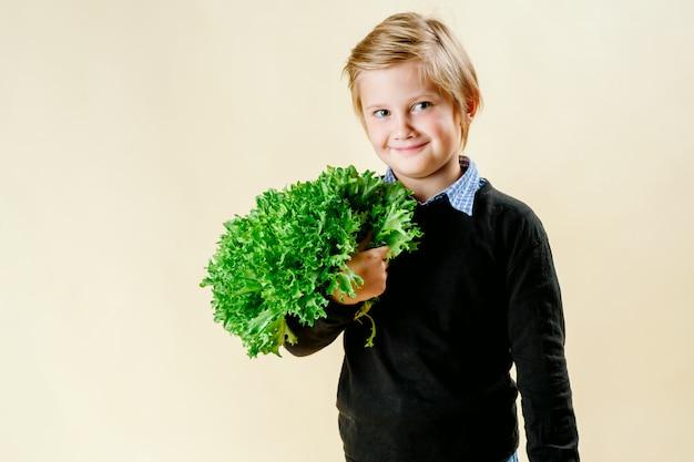 Un ragazzo dai capelli biondi tiene in mano la lattuga, una corretta alimentazione.