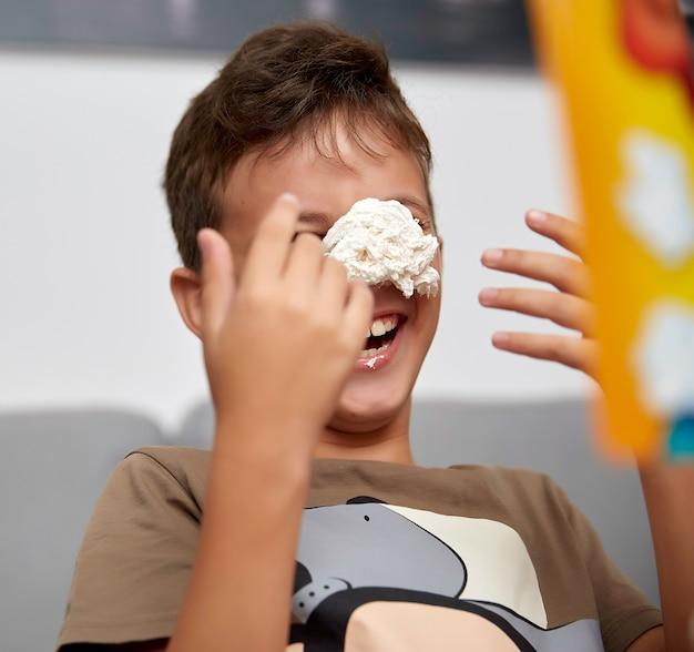Un ragazzo di dieci anni che gioca un gioco divertente con crema dolce, crema in faccia