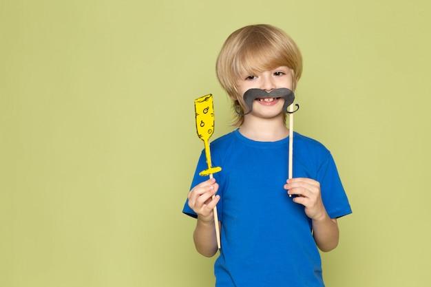 Un ragazzo divertente biondo di vista frontale in maglietta blu che tiene i baffi e la figura di vetro sullo spazio colorato pietra