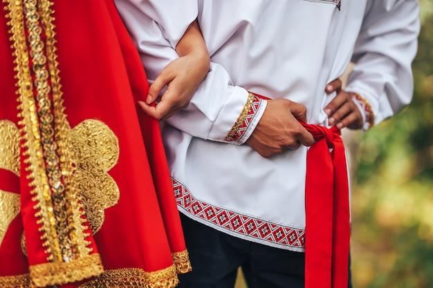 Un ragazzo e una donna vestiti con abiti nazionali russi si tengono per mano