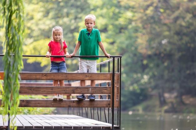 Un ragazzo e una ragazza di due bambini che stanno sulla piattaforma di legno su una riva del lago.