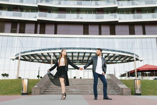Un ragazzo e una ragazza in abiti scuri si tengono per mano sullo sfondo di un edificio di vetro