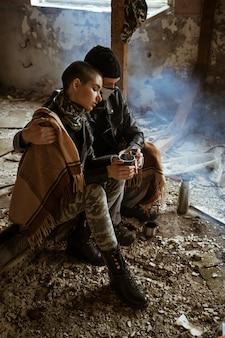Un ragazzo e una ragazza in una baraccopoli siedono insieme, il romanticismo dell'apocalisse