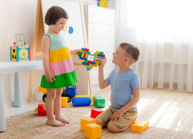 Un ragazzo e una ragazza tengono il cuore fatto di blocchi di plastica. fratello e sorella si divertono a giocare insieme