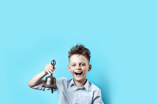 Un ragazzo felice in camicia leggera va a scuola. ha una campana in mano, che suona e sorride.