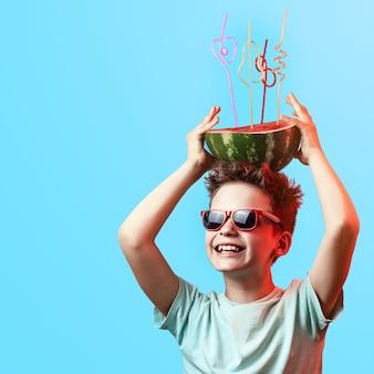 Un ragazzo felice in occhiali da sole che tengono anguria con i tubi del cocktail sulla testa sull'azzurro