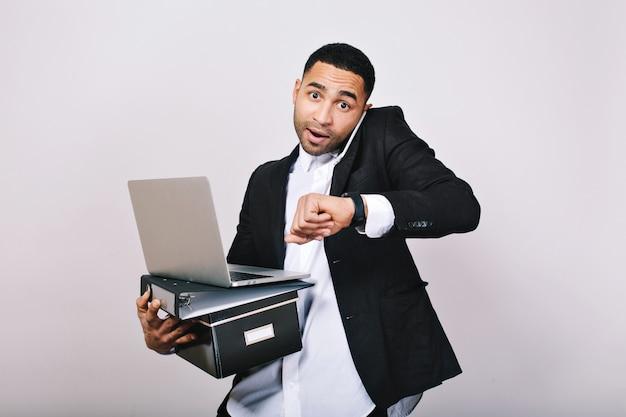Un ragazzo impegnato e laborioso in camicia bianca e giacca nera parla al telefono, tiene in mano cartelle, laptop, guarda stupito all'orologio. impiegato, tecnologia moderna, carriera.