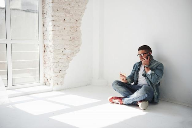 Un ragazzo in abiti casual è seduto a casa in un appartamento vuoto e chiama al telefono.