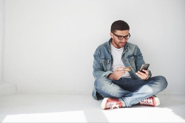 Un ragazzo in abiti casual è seduto a casa in un appartamento vuoto in possesso di una carta di credito