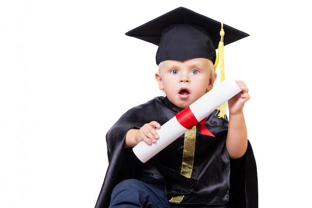 Un ragazzo in uno scapolo o in un vestito matrice con il rotolo del diploma isolato