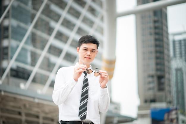 Un ragazzo intelligente è in piedi in città, indossa camicia bianca e cravatta.