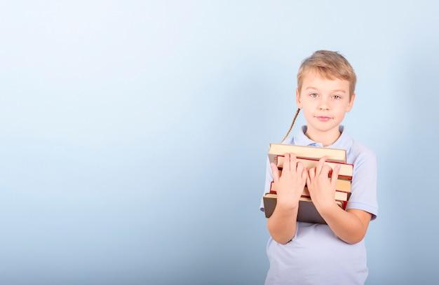 Un ragazzo legge un libro su uno sfondo blu, un concetto di educazione, scuola e lettura dell'amore