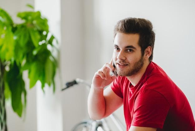 Un ragazzo parla con il cellulare a casa