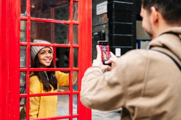 Un ragazzo scatta una foto con il cellulare di una ragazza in un cappotto giallo e un cappello di lana in una cabina rossa in una strada di londra