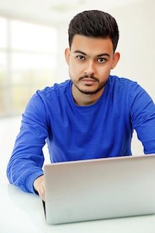 Un ragazzo seduto a un laptop in cerca di lavoro, che fa affari su internet. sulla luce